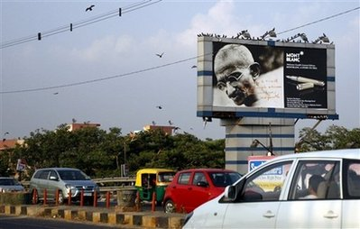 Traffic moves past a billboard displaying a portrait of Mohandas Gandhi, the ascetic father of India's independence, besides an image of a Montblanc pen in India.
